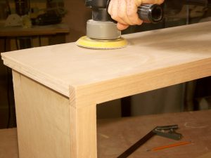sanding the cabinets to prepare for new faces